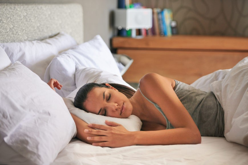 Attractive young woman peacefully sleeping in her bedroom in a tank top