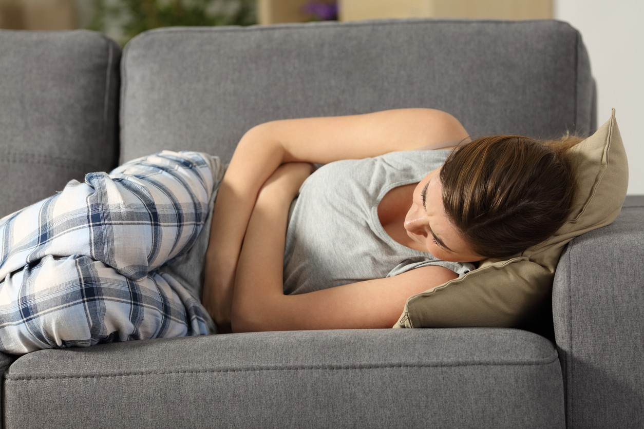Teen suffering belly-ache lying on a sofa in the living room at home