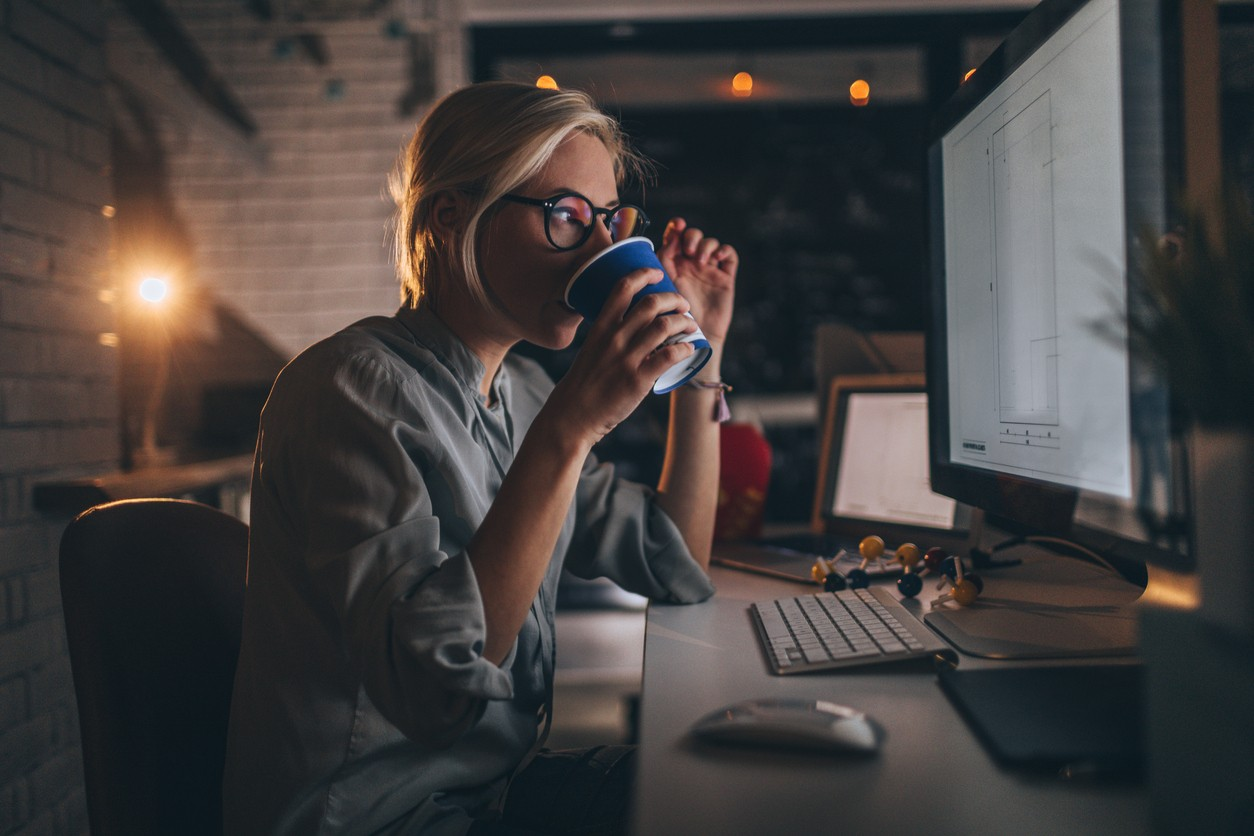 Photo of a young woman sitting at her desktop computer, having some hot coffee to help her stay up to wedding plan