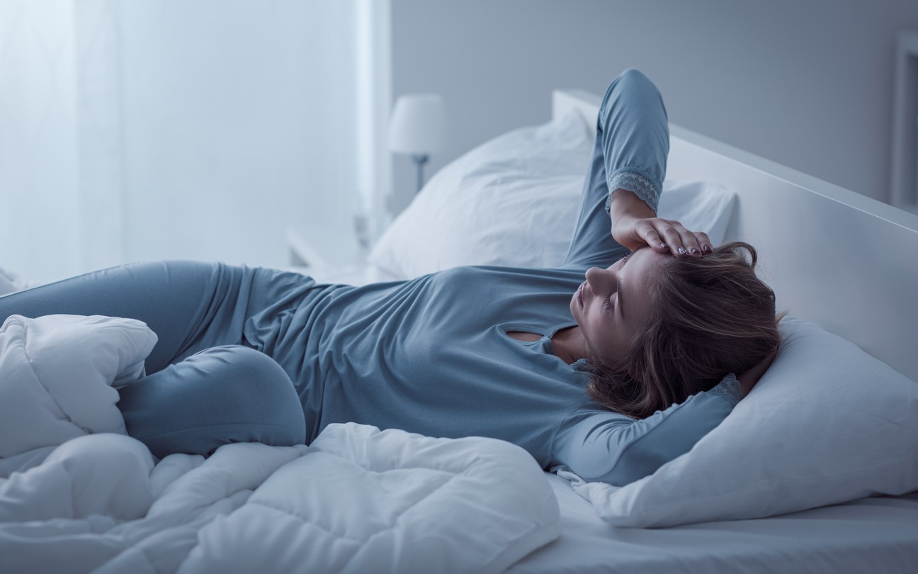 restless woman not awake in her bed, not able to fall asleep.