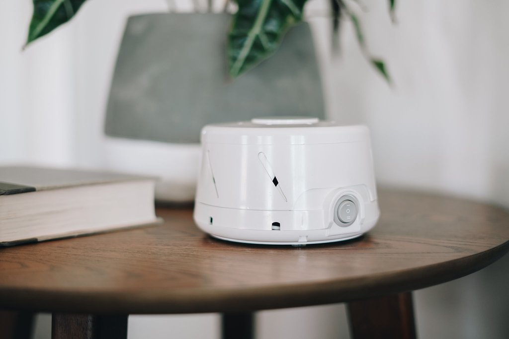 Marpac's Dohm Classic White Noise Machine on a bedside table.