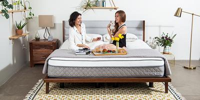 Two women chatting and having breakfast on a Nest Bedding mattress in the pajamas