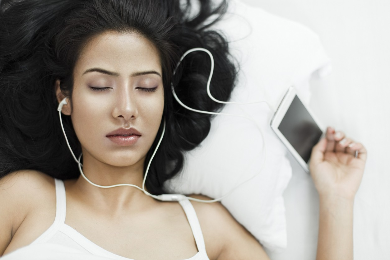 Brightly lit isolated image on white background of an Asian young woman with black and long hair in white spaghetti strap top. She is lying or sleeping on white bed and pillow with closed eyes and listening songs with earphones on through a smart phone.