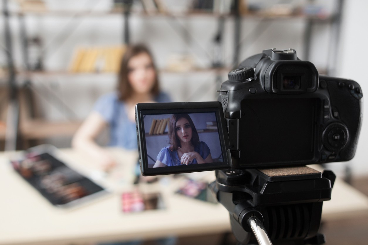 Young female beauty blogger on camera screen recording ASMR video