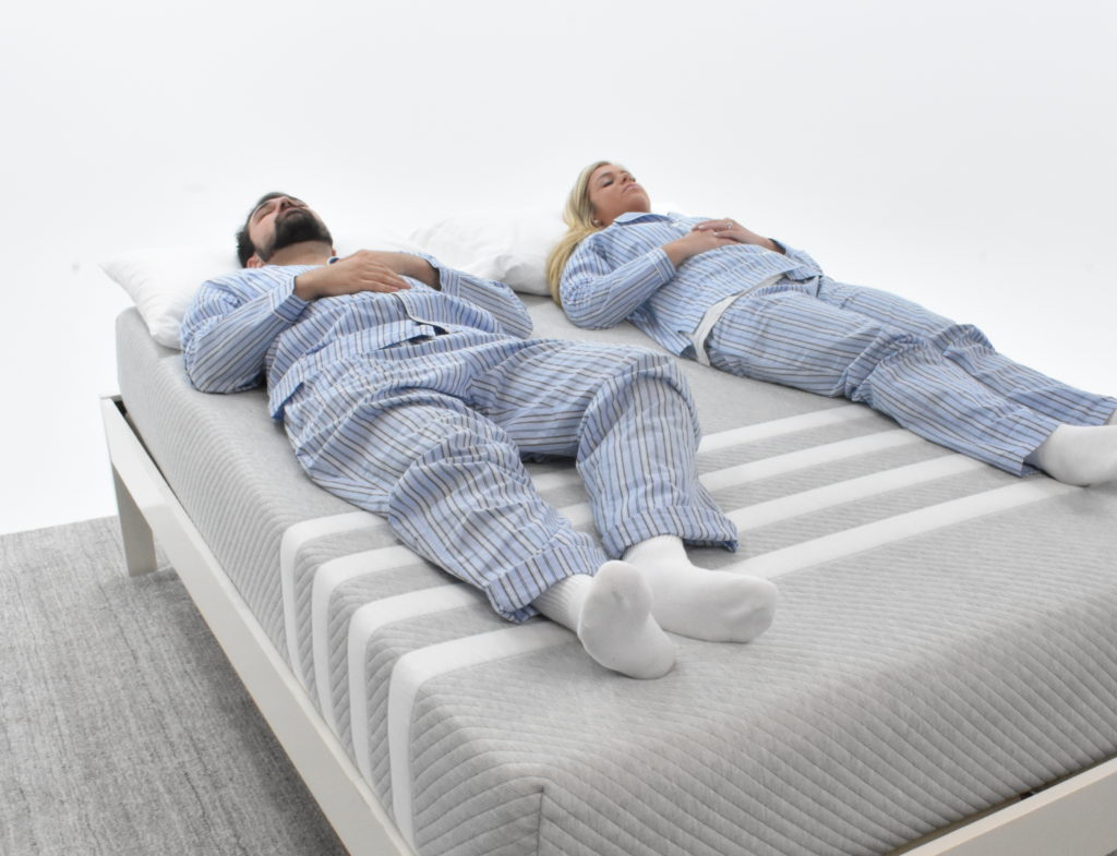 Man and woman laying on the Leesa mattress testing the responsiveness of the mattress