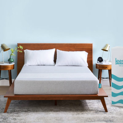 Leesa mattress on a bed frame in a bedroom with a product box beside the bed