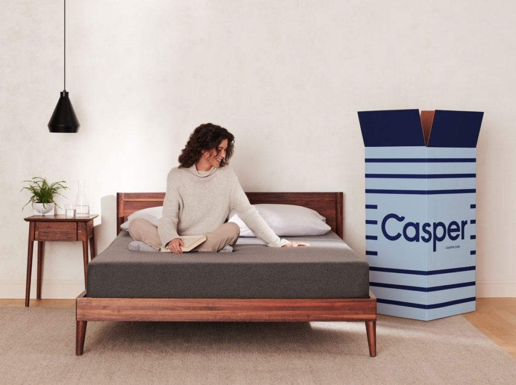 lady sitting on the edge of the Casper Essential mattress in a bedroom