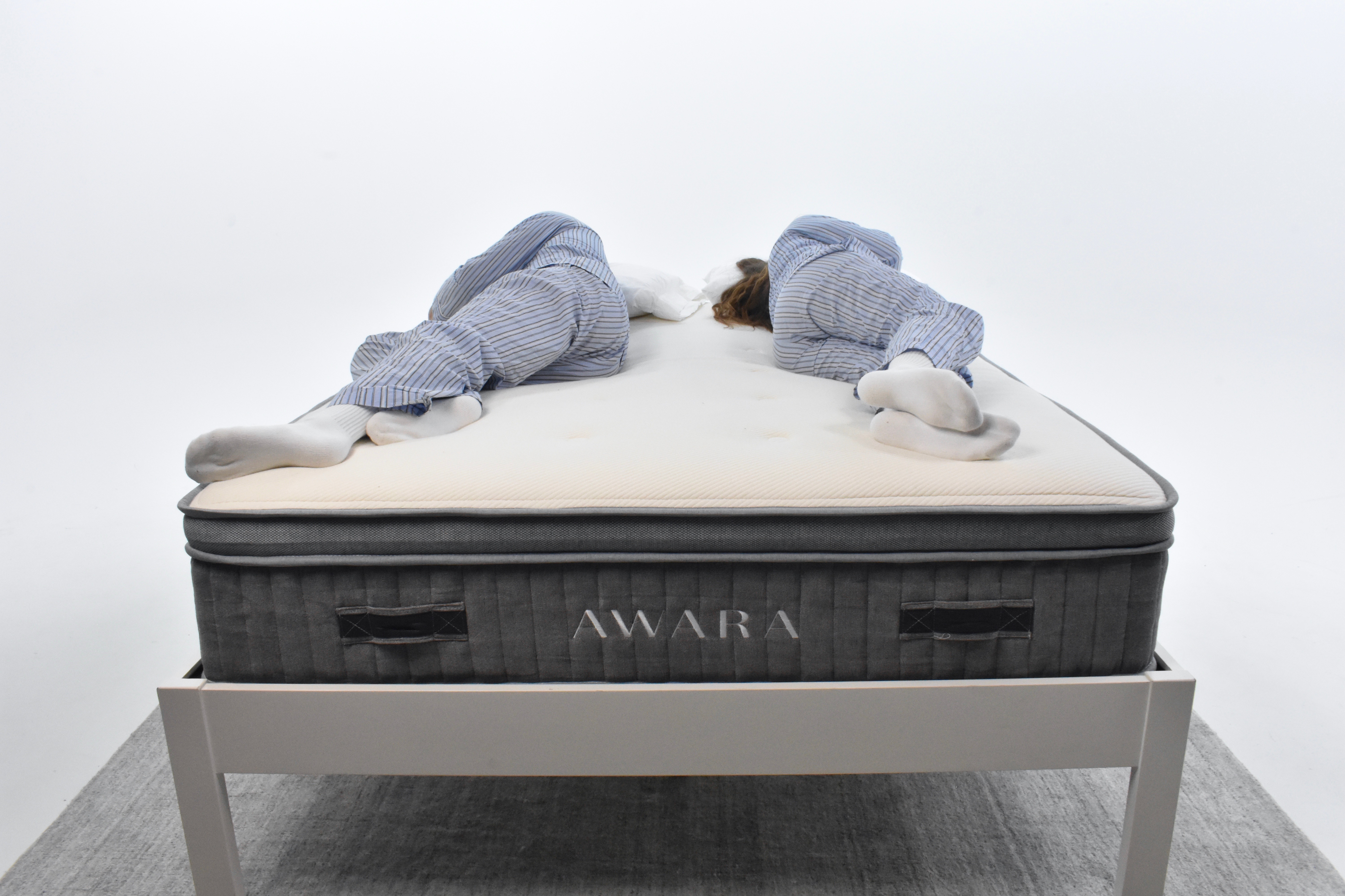 Man and woman laying on the Awara testing the responsiveness of the mattress