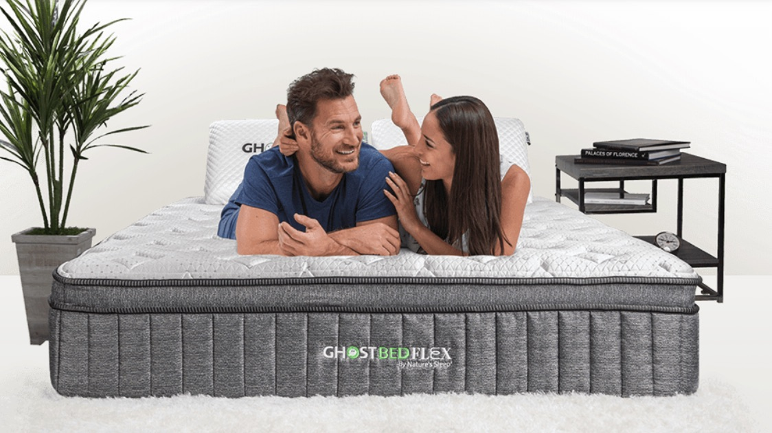 Man and woman laughing while laying on the GhostBed Flex