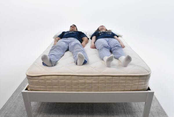 man and woman laying on mattress