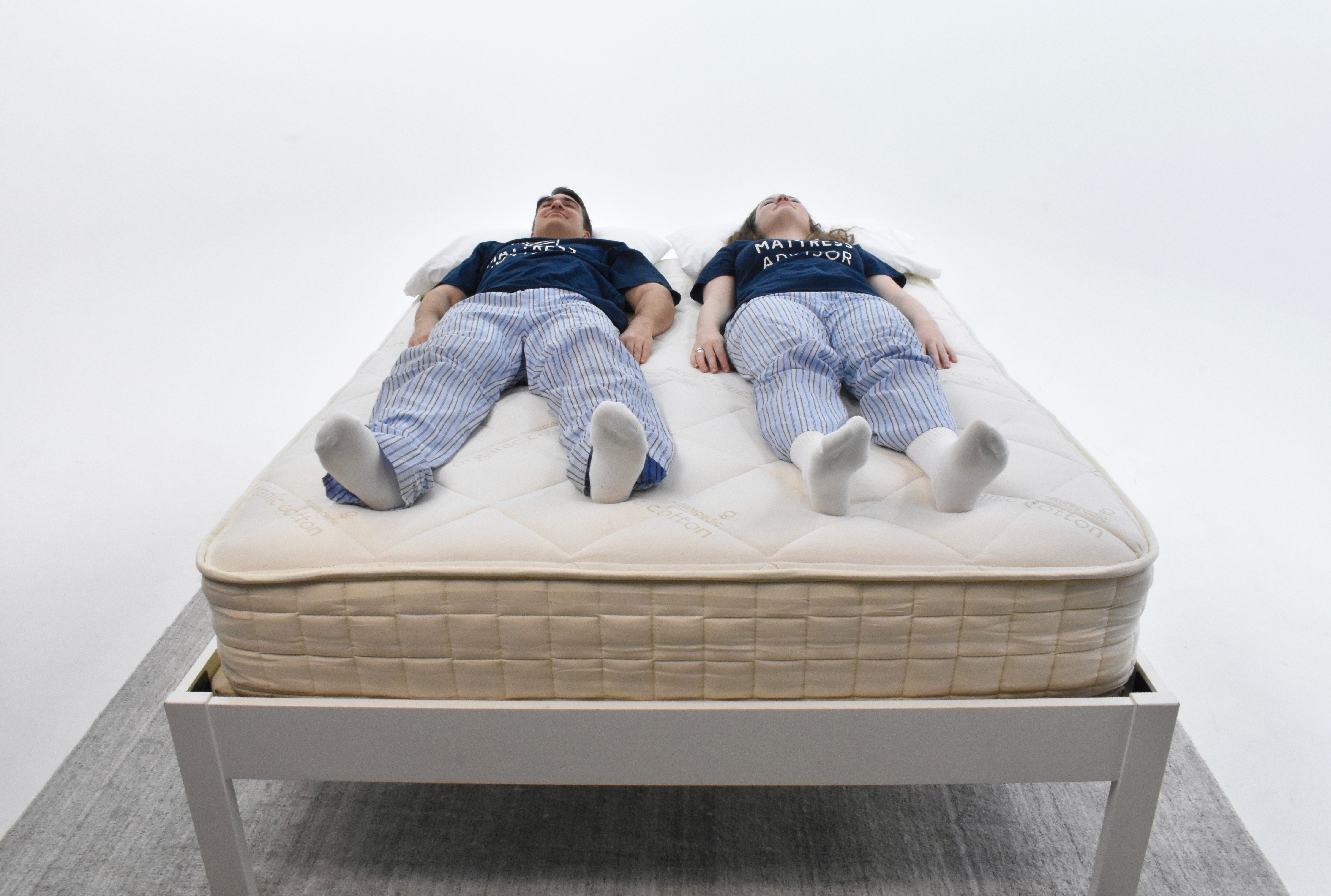 man and women laying on the naturepedic serenade mattress in a photo studio