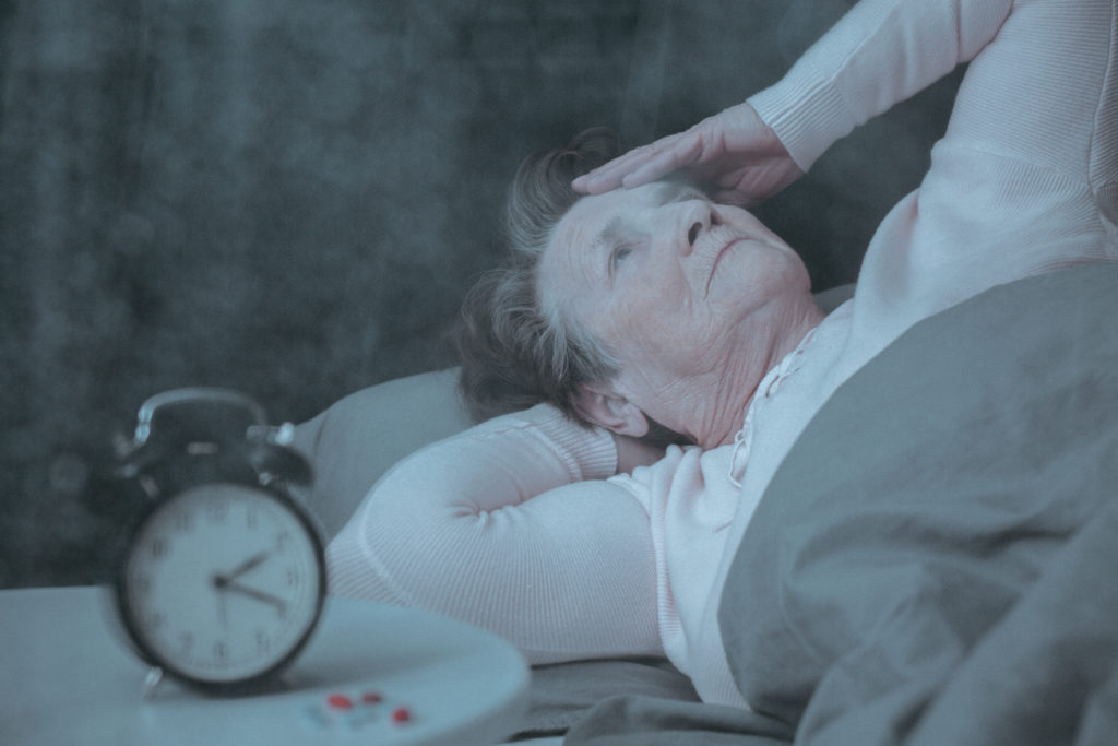 Senior woman with sleep disorder lying in bed