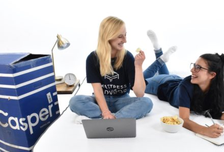 Two members of the Mattress Advisor team sitting on the Casper Hybrid mattress working on their laptops.