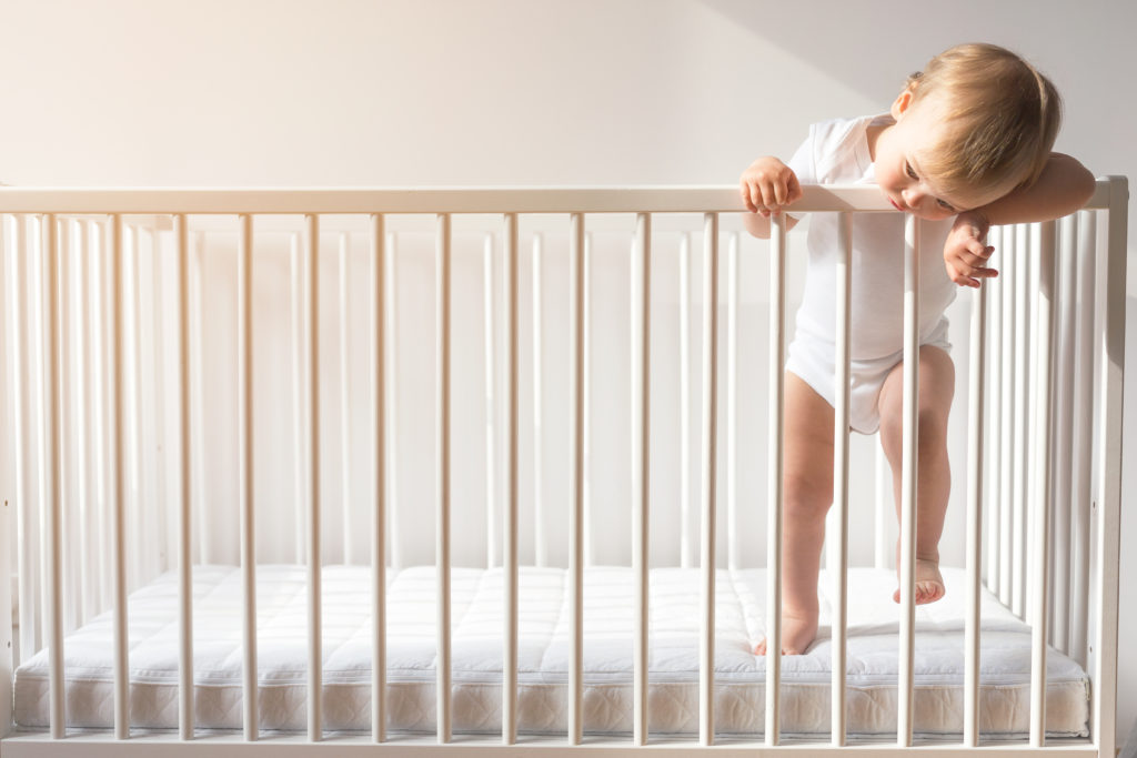 Portrait of a bored baby standing in a crib.