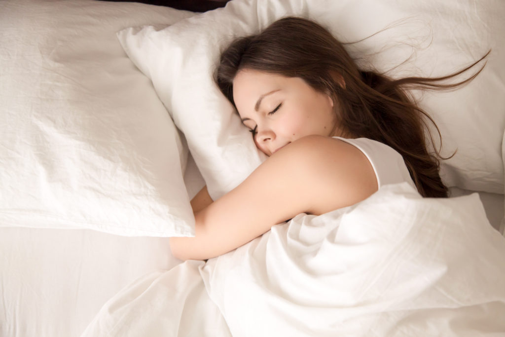 Top view of attractive young woman sleeping well in bed hugging soft white pillow. Teenage girl resting, good night sleep concept. Lady enjoys fresh soft bedding linen and mattress in bedroomTop view of attractive young woman sleeping well in bed hugging soft white pillow. Teenage girl resting, good night sleep concept. Lady enjoys fresh soft bedding linen and mattress in bedroom