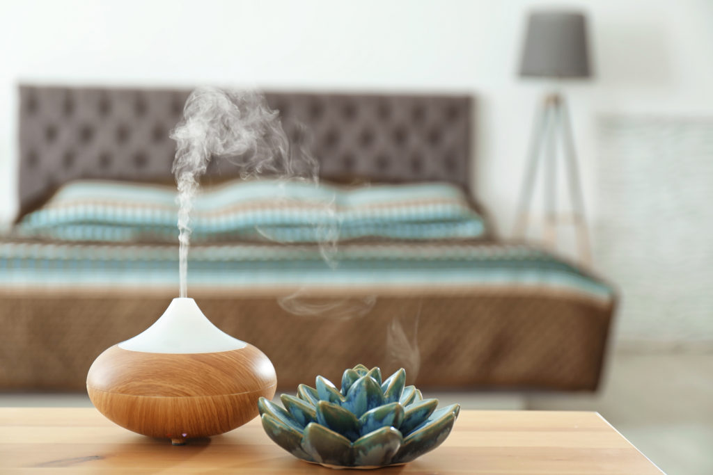 Aroma oil diffuser on table at home