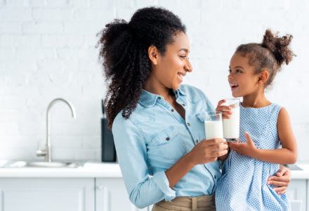 smiling african american mother and daughter holding glasses of milk in kitchen and looking at each other