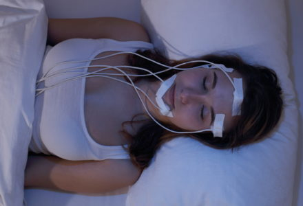 woman hooked up for sleep study at night at sleep clinic