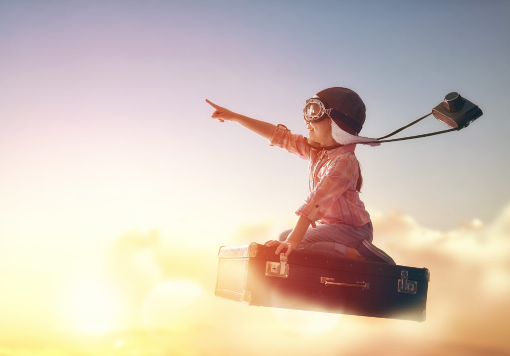 kid flying on suitcase in clouds in a dream