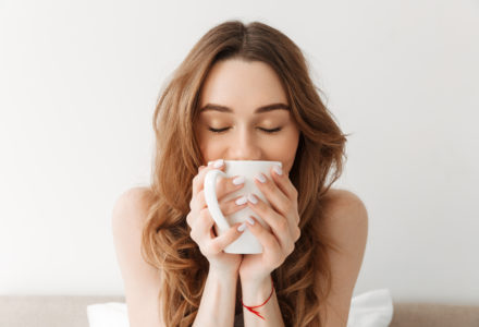 Portrait of lovely woman with beautiful brown hair drinking morning coffee or tea while resting in bed