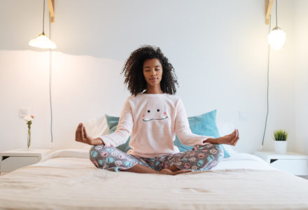 Happy beautiful young woman relaxed at home doing morning meditation in bed